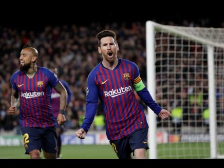 Barcelona's Lionel Messi (right) celebrates after scoring his side's third goal during the Champions League round-of-16, second-leg match against Olympique Lyon at the Camp Nou stadium in Barcelona, Spain, yesterday.