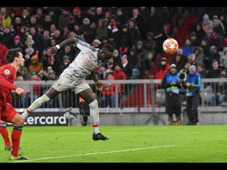 Liverpool midfielder Sadio Mane (second left) scores his side's third goal during the Champions League round-of-16 second leg match between Bayern Munich and Liverpool at the Allianz Arena, in Munich, Germany, yesterday.