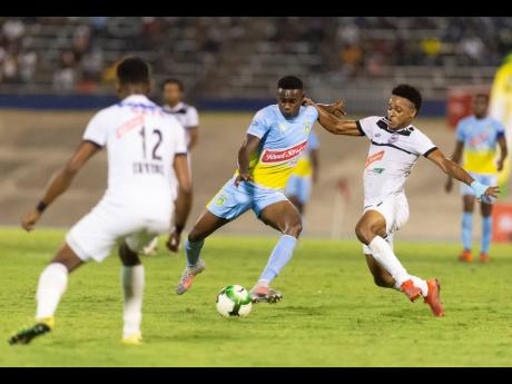 Andre Leslie (left) of Waterhouse FC is contested by Cavalier FC's Alex Marshall in the Red Stripe Premier League first-leg, semi-final match last week. Waterhouse lead 2-0 ahead of the second leg tonight.