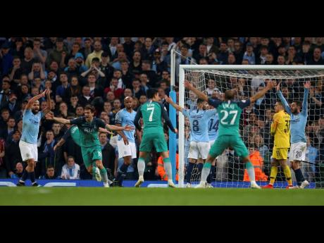 Tottenham's Fernando Llorente (second left) celebrates scoring his side's third goal as Manchester City's Sergio Aguero (left) appeals for handball, watched by Manchester City's Vincent Kompany (third left) during their second leg UEFA Champions League quarter-final match at the Etihad Stadium in Manchester, England, yesterday.