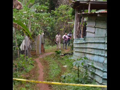 Police personnel view the charred remains of Miguel Williams, who it is believed was beaten and burnt to death by residents.