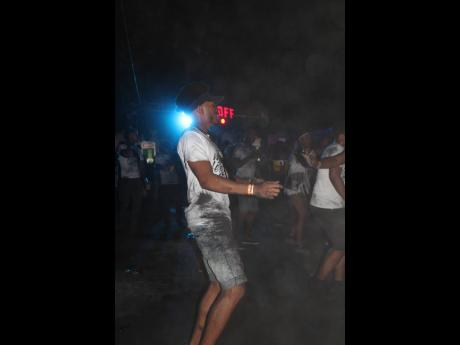 A cloud of charcoal almost blinds this patron but he continues to enjoy the festivities at ASH J'ouvert.