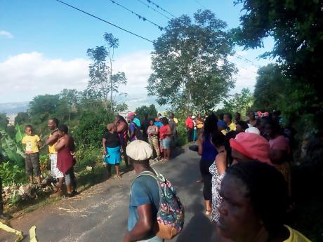 Residents of Bellefield stand along the roadway near the murder scene.