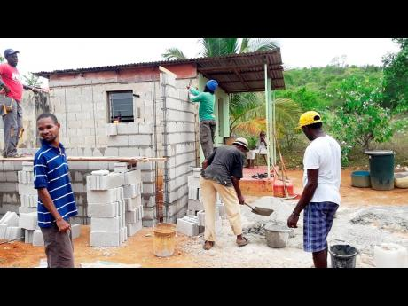Workmen construct the bathroom to Miss Eda's home.