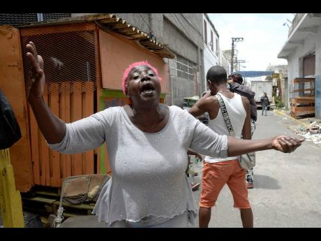 Andrea Gordon pleads for help after losing most of her belongings in a fire on Matthews Lane in downtown Kingston yesterday.