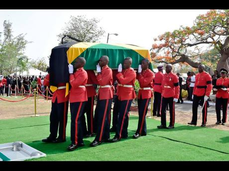 Members of the Jamaica Defence Force take Edward Seaga to his final resting place in National Heroes Park in Kingston yesterday.