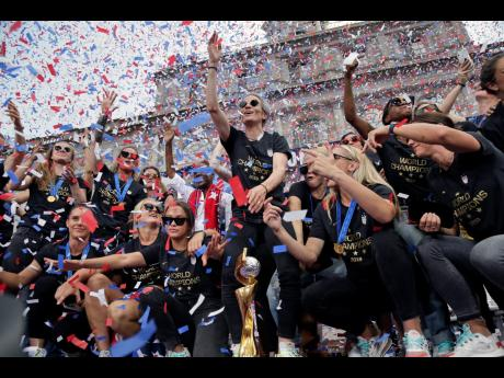 The US senior women's football team, and captain Megan Rapinoe (center), celebrate with the FIFA Women's World Cup trophy at City Hall after a ticker tape parade in New York City yesterday. (AP Photo/Seth Wenig)