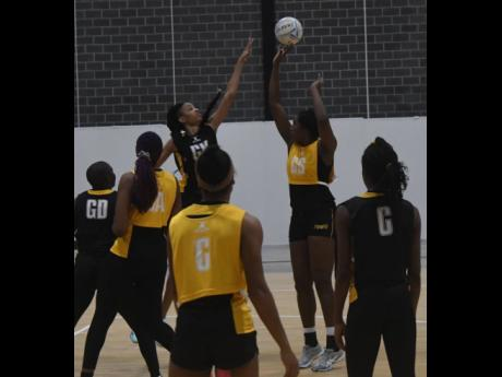 Sunshine Girls captain Jhaniele Fowler (second right) takes a shot on goal while challenged by goalkeeper Shamera Sterling, during a training session on Wednesday, ahead of their opening Netball World Cup game against Fiji today.