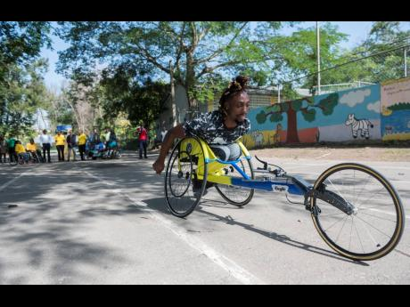 Keino Hewitt gets a feel of his new racing wheelchair, moments after the handover at the Sir John Golding Rehabilitation Centre on Thursday July 4, 2019. The chair gifted by the Tony Thwaites Wing will aid Hewitt in his aim to compete in the 2020 Paralympic Games. Representatives from the Tony Thwaites wing, University of Technology Jamaica, Jamaica Paralympic Association, and Sir John Golding Rehabilitation Centre were present.