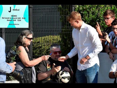 Defender Matthijs de Ligt (right) is greeted by fans upon his arrival at the Juventus Medical Center in Turin, Italy, yesterday.