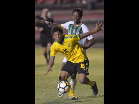 Nicque Daley shields the ball from Dominica defender Jolly Fitz.