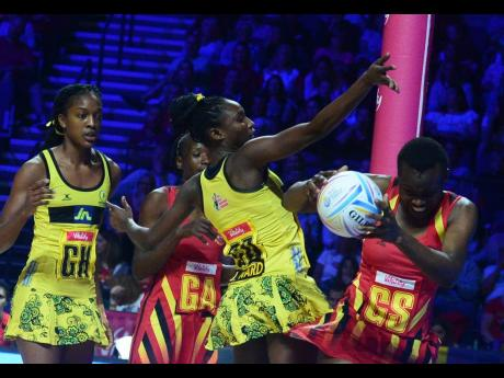 Jamaica's Jodian Ward (second right) challenges Uganda's Stella Oyella (right) for the ball as Kadie-Ann Dehaney (left) and Racheal Nanyonga look on.