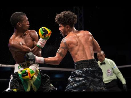 Toriano Nicholas (left) of Jamaica receives a hard left to the body by American boxer Carlos Dixon during the Gloves Over Guns fight night held at the Ambassador Theatre in Trench Town, Kingston, on Saturday, July 13.