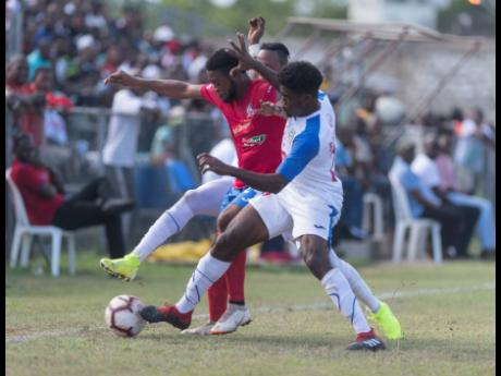 Dean-Andre Thomas of Dunbeholden (left) is contested by Roshane Sharpe of Portmore United for possession of the ball in their Red Stripe Premier League match at the Spanish Town Prison Oval on September 15.