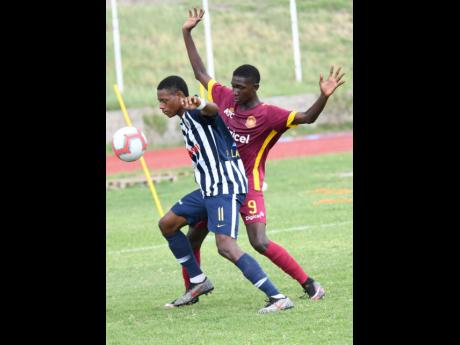 Rushane Thompson (right) of Wolmer's and Phillon Lawrence of Jamaica College challenge for the ball during the ISSA/Digicel Manning Cup matchup between Wolmer's and Jamaica College at Stadium East on Monday.