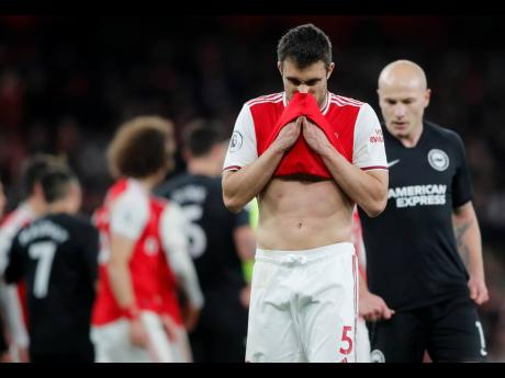 Arsenal's Sokratis Papastathopoulos wipes his face during the English Premier League match between Arsenal and Brighton, at the Emirates Stadium in London, yesterday.