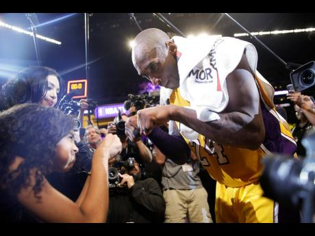 In this April 13, 2016 file photo Los Angeles Lakers' Kobe Bryant (right) fist-bumps his daughter Gianna after the last NBA basketball game of his career, against the Utah Jazz in Los Angeles, California.