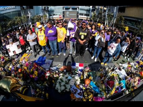 People gather at a memorial for Kobe Bryant near Staples Center in Los Angeles, California, yesterday.