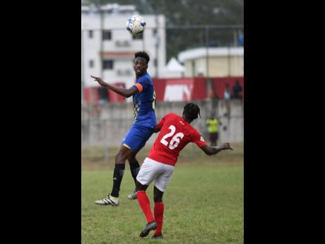 Molynes United's Nicholas Nelson (left) heads the ball away from UWI's Javoy Blenavis in their Red Stripe Premier League encounter at the UWI Mona Bowl on Sunday.