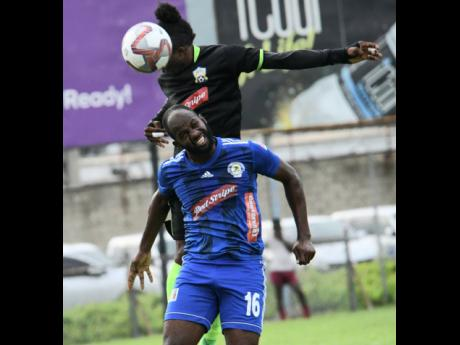 Mount Pleasant's Francois Swaby (front) goes up for a header with Molynes United's Andrew Peddlar during  a Red Stripe Premier League encounter at the Waterhouse Mini Stadium in October last year.