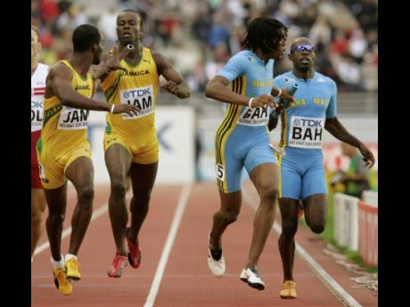 Troy McIntosh (right) hands off to Bahamas relay team member Andrae Williams as Lansford Spence (second left) hands off to Jamaican relay team member Davian Clarke during the first men's 4x400 relay heat at the World Athletics Championships in Helsinki on August 13, 2005.