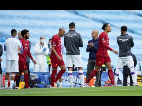 Liverpool players walk through a guard of honor from the Manchester City team ahead of their English Premier League match at Etihad Stadium in Manchester, England, Thursday, July 2, 2020.