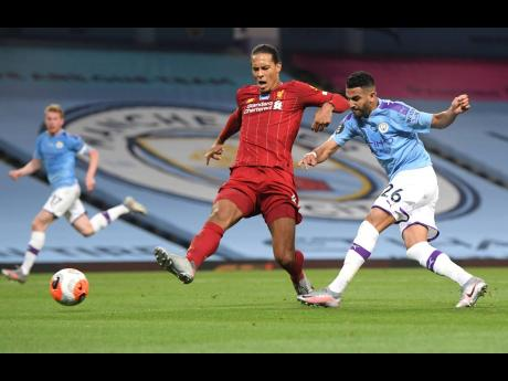 Manchester City's Riyad Mahrez (right) attempts a shot on goal during the English Premier League match between Manchester City and Liverpool at Etihad Stadium in Manchester, England, Thursday, July 2, 2020.