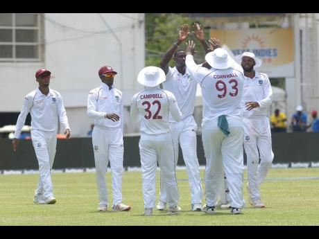 Jason Holder (third right) celebrates with teammate Rahkeem Coornwall who caught India's Marayank Agarwal off his delivery on day one of their second Test match at Sabina Park in Kingston, Jamaica, on Friday, August 30, 2019.
