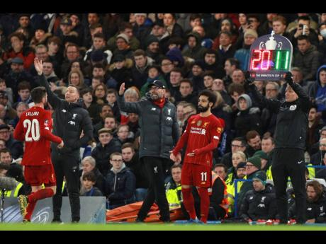 Liverpool's manager Jurgen Klopp (centre) shouts out from the touchline as Liverpool's Adam Lallana (left) is substituted by Liverpool's Mohamed Salah during the English FA Cup fifth round match between Chelsea and Liverpool at Stamford Bridge stadium in London, Tuesday, March 3, 2020.