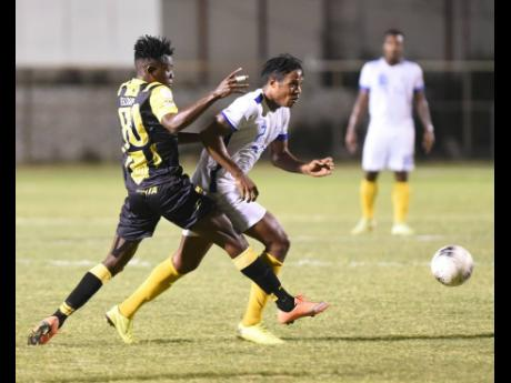Waterhouse's Stephen Williams dribbles away  from Elliader Dorius of Don Bosco from Haiti in their Concacaf club match at the Anthony Spaulding Sports Complex on February 2.