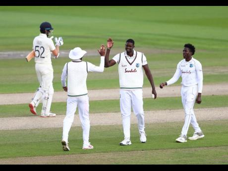 West Indies captain Jason Holder (second right) celebrates with teammates the dismissal of England's Dom Sibley (left) during the third day of the third Test match at Old Trafford in Manchester, England, in July.