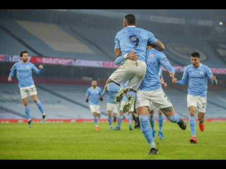 Manchester City players celebrate after scoring their team second goal during the English Premier League match between Manchester City and Wolves at the Etihad stadium in Manchester, England, yesterday.