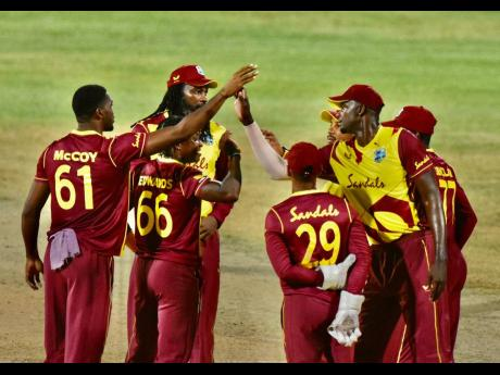 West Indies players huddle as they celebrate taking a wicket against Sri Lanka in the first match of the T20I series yesterday.