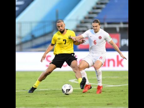 Kemar Roofe (left) of Jamaica is challenged by Canada's Samuel Piette during Sunday's Concacaf World Cup qualifier at the National Stadium.